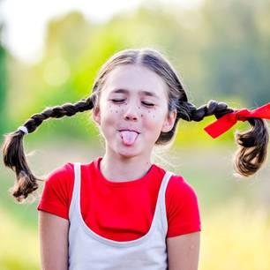 Pippi Langstrumpf Sprüche: Mädchen mit Zöpfen streckt die Zunge heraus
