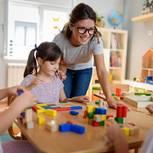 Erzieherin und Kinder spielen mit Holzklötzen