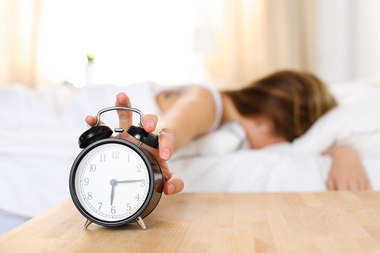 Optimale Schlafenszeit: Frau versucht, Wecker auszuschalten