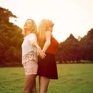Zwei junge Frauen auf Wiese Rücken an Rücken