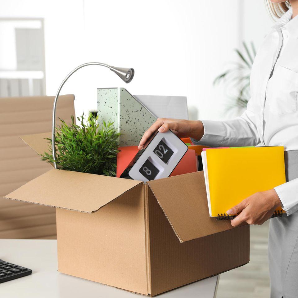 Frau packt ihre Sachen in einen Karton