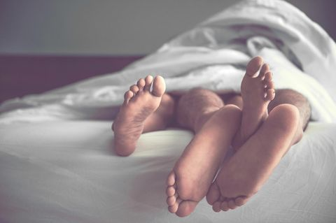 Füße von Paar im Bett