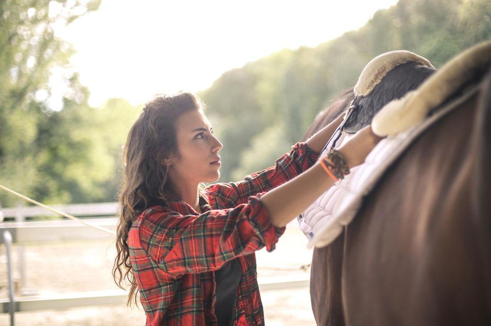 Frau sattelt ein Pferd auf