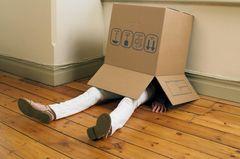 Was kinderlose Frauen nicht mehr hören wollen: Eine Frau versteckt sich unter einem leeren Umzugskarton