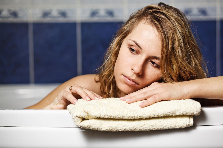 Traurige Frau in Badewanne