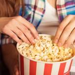 Mann und Frau essen Popcorn im Kino