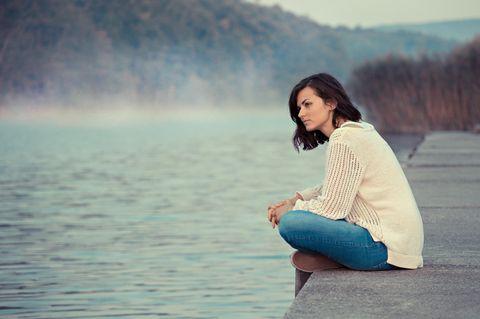 Schlechte Laune: Eine nachdenkliche Frau sitzt am See