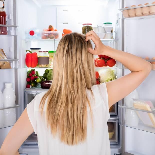 Naschen und schlechtes Gewissen: Frau vorm Kühlschrank