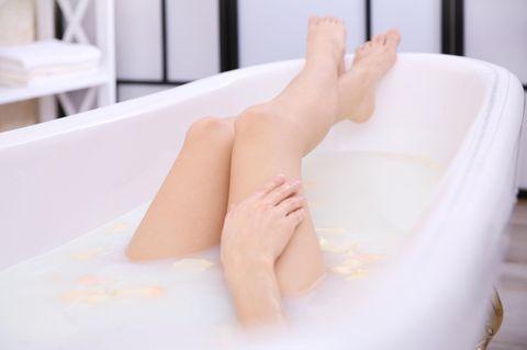 Beine einer Frau beim Milchbad