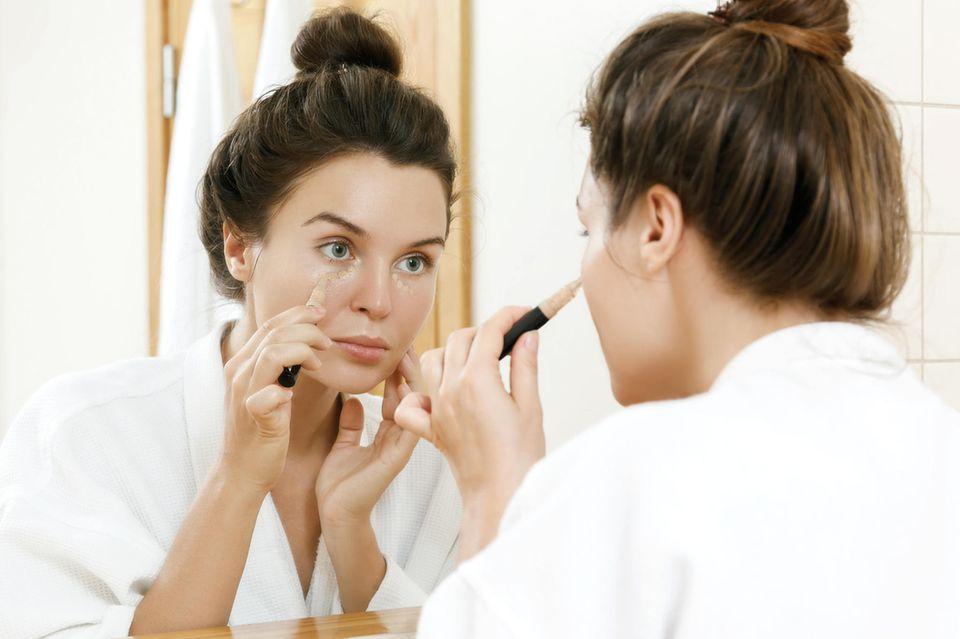 Concealer: Frau trägt Concealer unter den Augen auf