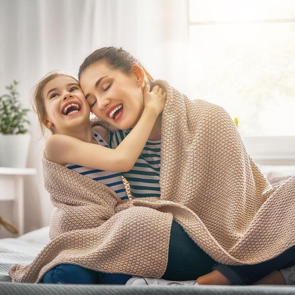Mutter und Tochter unter Wolldecke