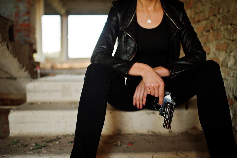 Frau mit Revolver sitzt auf Treppe
