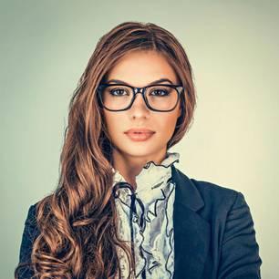 Frau mit Brille posiert für Passfoto