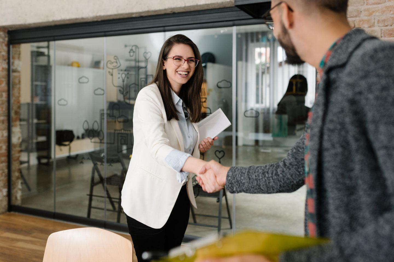 Personalmanager: Frau gibt Mann die Hand im Büro