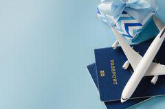 Reise-Geschenke: Modellflugzeug auf Reisepass, daneben ein Geschenk