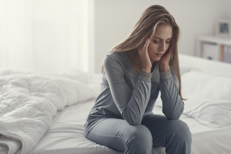 Frau mit Kopfschmerzen sitzt auf Bett