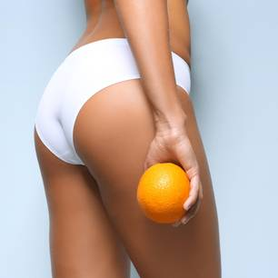 Frau hält Orange vor ihren Po