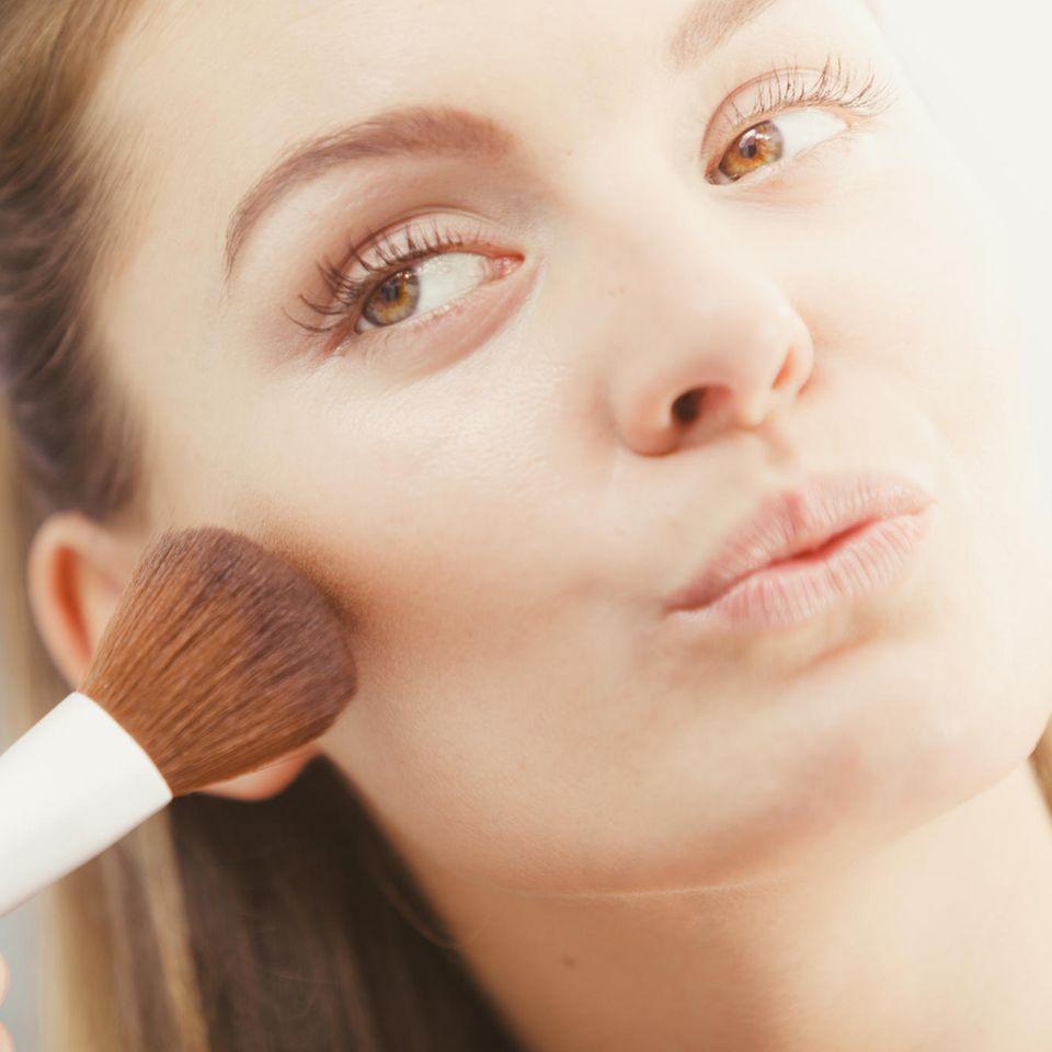Frau pudert sich das Gesicht