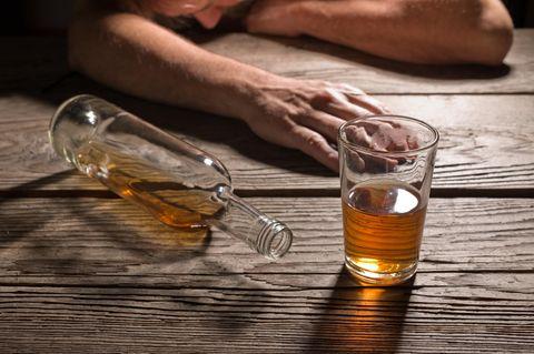 Brandyflasche und Glas vor betrunkenem Mann