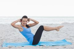 Frau macht Pilates am Strand