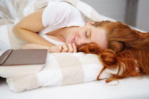 Horoskop: Eine lächelnde Frau im Bett