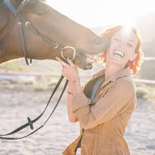 Rothaarige Frau wird von Pferd geküsst