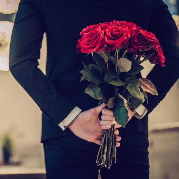 Horoskop: Ein Mann im Anzug mit einem Strauß Rosen hinterm Rücken