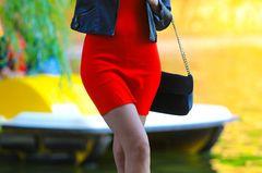 Frau in kurzem roten Kleid und Jacke