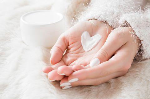 Creme-Herz auf Handfläche