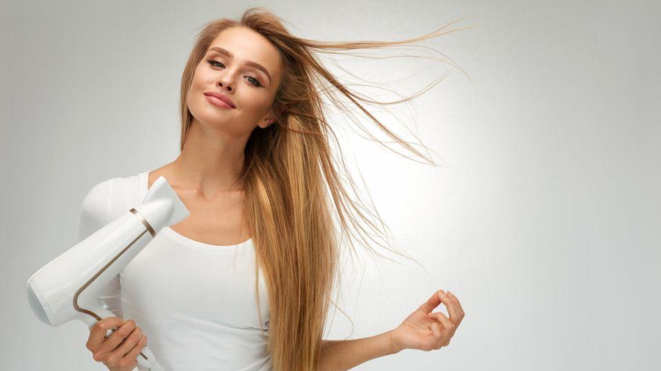 Frau in weiß föhnt sich die Haare