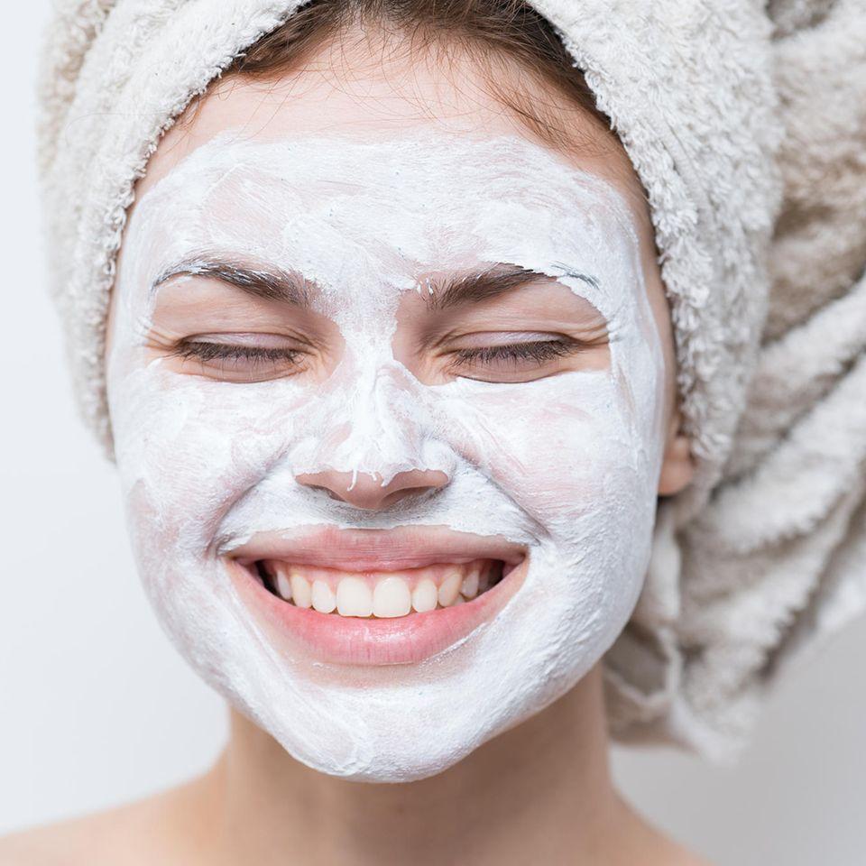 Frau mit Creme im Gesicht und Handtuch