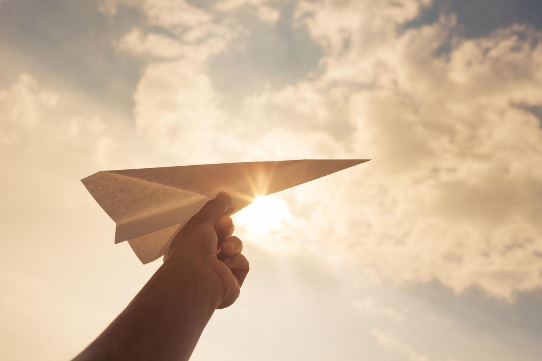 Papierflugzeug wird vor die Sonne gehalten