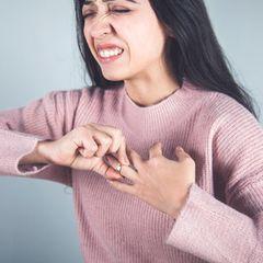 Frau versucht einen Ring vom Finger zu ziehen