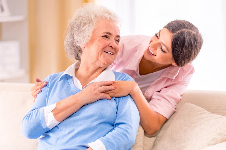 Altenpfleger: Frau kümmert sich um ältere Frau