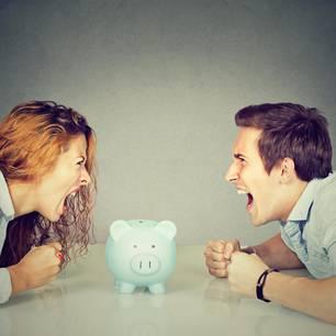 Mann und Frau schreien sich über ein Sparschwein an