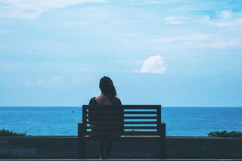 Frau auf Bank schaut auf das Meer