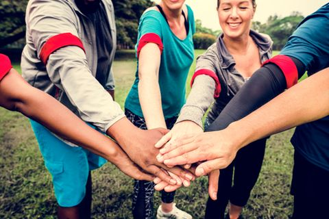 Teambuilding-Ideen: Eine Gruppe von Menschen hält die Hände aufeinander