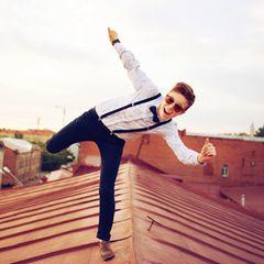 teambuilding-ideen: Junger Mann balanciert auf einem Dach