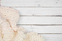 Weiße Decke auf weißem Holztisch