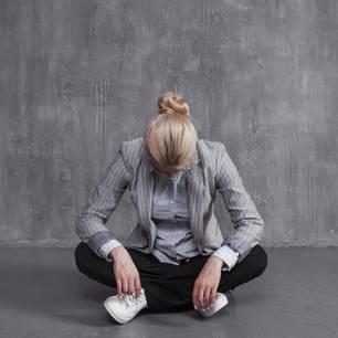Frau im Schneidersitz vor grauer Wand