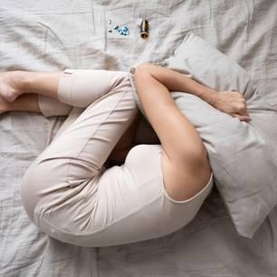 Depressive Frau im Bett mit Kissen über Kopf und Tabletten