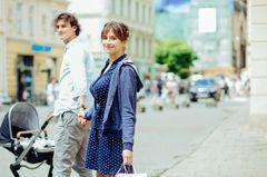 Paar mit Kinderwagen in der Stadt