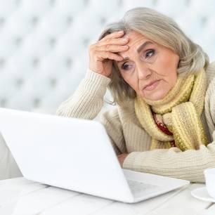 Ältere, verzweifelte Dame vor ihrem PC