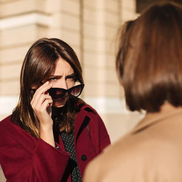 Wie erkennt man schlechte Zuhörer? Eine Frau schaut ihr Gegenüber über eine Sonnenbrille hinweg fragend an