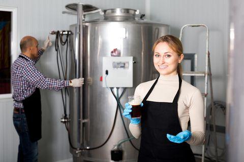 Brauer: Frau vor Brauerei-Equipment
