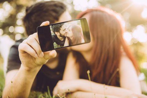 Liebe in sozialen Medien: Ein Paar küsst sich und macht dabei ein Selfie