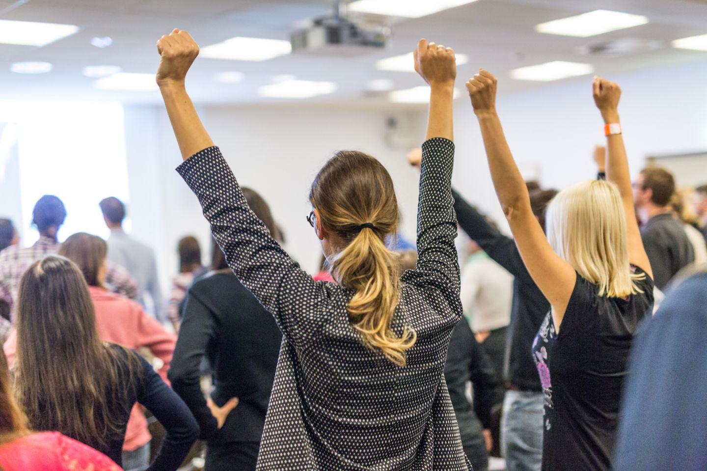 Life Coach Trends: Frau die motiviert ihre Arme nach oben hebt