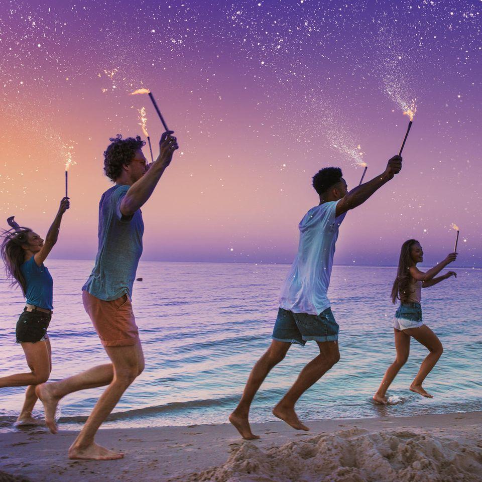 Sternzeichen und die vier Elemente: Freunde laufen mit Wunderkerzen am Meer entlang