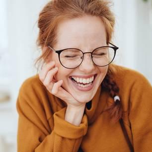 Horoskop: Eine rothaarige Frau mit Hornbrille lacht aus vollem Herzen