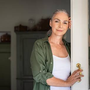 Umzug im Alter: Ältere Dame lehnt an Tür